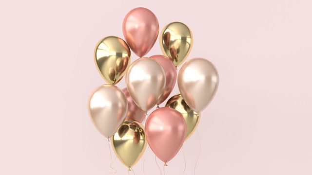 Floating balloons in front of a light pink background.